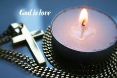 Dieu est amour avec la croix d'or avec la bougie de thé de haute qualité Image stock