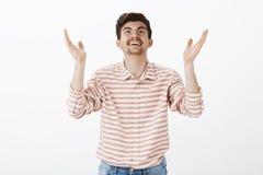 Dieu merci c'est vendredi Portrait de professeur masculin réussi reconnaissant dans la chemise rayée, soulevant des mains et rech Photographie stock