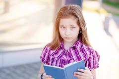 Diez años de la colegiala observada azul que lee un libro Fotografía de archivo