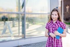 Diez años de la colegiala observada azul que sostiene un libro Imagen de archivo libre de regalías
