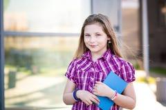 Diez años de la colegiala observada azul que sostiene un libro Foto de archivo libre de regalías