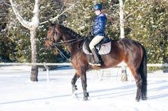 Diez años de muchacha que monta un caballo en invierno Foto de archivo