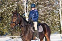 Diez años de muchacha que monta un caballo en invierno Imagen de archivo