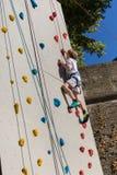 Diez años de muchacho que sube la pared artificial al aire libre con los controles coloridos modernos Foto de archivo