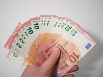 Diez billetes de banco euro avivados hacia fuera en la mano de un varón caucásico foto de archivo libre de regalías