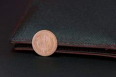 Diez monedas japonesas de los yenes en el JPY reverso con la cartera negra en piso negro fotos de archivo