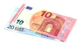 Diez y veinte euros en un fondo blanco Fotografía de archivo