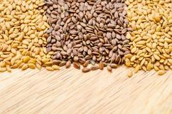 Diferença de linhaças douradas e de linhaças marrons (sementes de linho) fotos de stock