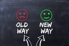 Diferencia entre la vieja manera y nueva la manera, ilustradas con las caras felices y tristes en la pizarra fotografía de archivo libre de regalías