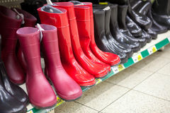Diferent red and black waterboots are on shop shelves Stock Image