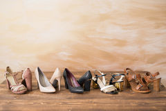 Diferent style woman`s high heels on wooden floor Royalty Free Stock Photography