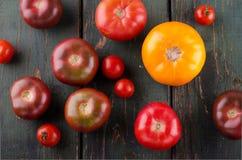 Diferentes tipos coloridos de tomates en fondo de madera Foto de archivo libre de regalías