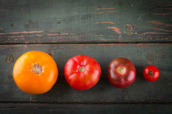 Diferentes tipos coloridos de tomates en fondo de madera Imágenes de archivo libres de regalías