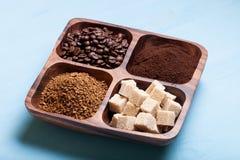 Diferentes tipos de café en la placa de madera en la tabla azul Imagen de archivo