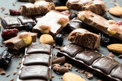 Diferentes tipos de chocolate y de frutas secadas en un fondo negro fotografía de archivo libre de regalías
