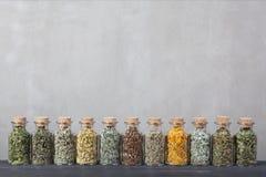 Diferentes tipos de hierbas para el té dentro de las botellas de cristal Fotografía de archivo libre de regalías