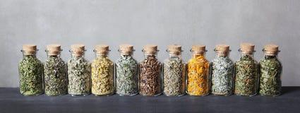 Diferentes tipos de hierbas para el té dentro de las botellas de cristal Foto de archivo