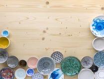 Diferentes tipos de loza colorida moderna en diversos diseños en fondo de madera ligero imagenes de archivo