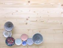 Diferentes tipos de loza colorida moderna en diversos diseños en fondo de madera ligero foto de archivo libre de regalías