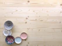 Diferentes tipos de loza colorida moderna en diversos diseños en fondo de madera ligero fotos de archivo libres de regalías