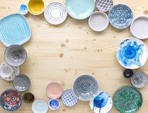 Diferentes tipos de loza colorida moderna en diversos diseños en fondo de madera ligero imagen de archivo libre de regalías