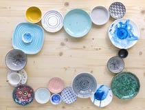 Diferentes tipos de loza colorida moderna en diversos diseños en fondo de madera ligero fotografía de archivo libre de regalías