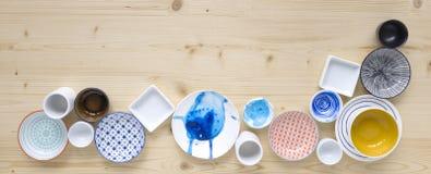 Diferentes tipos de loza colorida y blanca moderna en fondo de madera ligero imagen de archivo libre de regalías