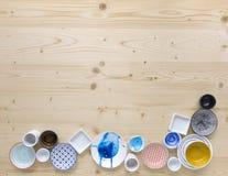 Diferentes tipos de loza colorida y blanca moderna en fondo de madera ligero imagen de archivo