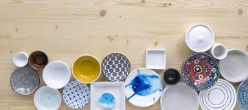 Diferentes tipos de loza colorida y blanca moderna en fondo de madera ligero imágenes de archivo libres de regalías