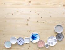 Diferentes tipos de loza colorida y blanca moderna en fondo de madera ligero fotografía de archivo libre de regalías