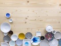 Diferentes tipos de loza colorida y blanca moderna en fondo de madera ligero foto de archivo