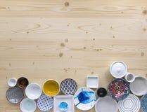 Diferentes tipos de loza colorida y blanca moderna en fondo de madera ligero fotos de archivo libres de regalías