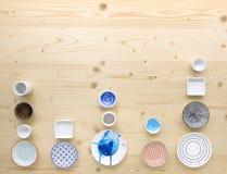Diferentes tipos de loza colorida y blanca moderna en fondo de madera ligero fotos de archivo