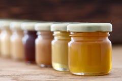 Diferentes tipos de miel en fila Foto de archivo libre de regalías