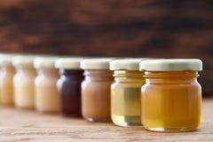 Diferentes tipos de miel en fila Fotos de archivo