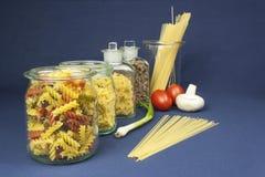 Diferentes tipos de pastas en la tabla, así como verduras Imagen de archivo