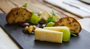 Diferentes tipos de queso, de uvas y de pan en fondo gris Foto de archivo
