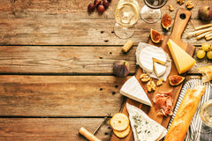 Diferentes tipos de quesos, de vino, de baguettes, de frutas y de bocados Foto de archivo
