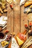 Diferentes tipos de quesos, de vino, de baguettes, de frutas y de bocados Foto de archivo libre de regalías