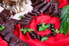 Diferentes tipos del caramelo de chocolate, rojo que cubre de la tela, aún vida, atmósfera, lujo Imagenes de archivo