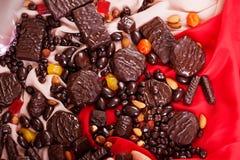 Diferentes tipos del caramelo de chocolate, rojo que cubre de la tela, aún vida, atmósfera, lujo Fotos de archivo libres de regalías