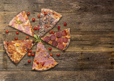 Diferents types of pizza cut on wooden table Stock Photo