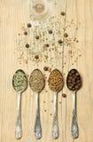 Différentes épices dans des cuillères d'argent sur le fond en bois Image libre de droits