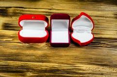 Différentes boîtes à bijoux rouges sur la table en bois Photo stock