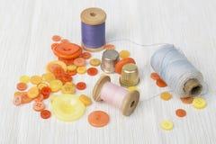 Différentes bobines de fil avec les boutons colorés et dés sur la surface légère Images libres de droits