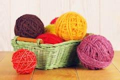 Différentes boules de fil dans le panier en bois Image stock