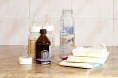 Différentes bouteilles en verre avec un mélange de l'alimentation et du diape de bébé Photo libre de droits