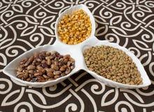 Différentes céréales, céréales Différents types de poussières abrasives dans des tasses sur un fond modelé Maïs, haricots Consomm image stock