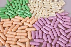 Différentes capsules renversées sur le fond blanc image stock