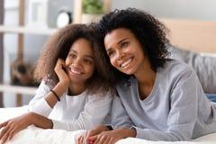 Différentes femelles d'âges de joli métis reposant le mensonge sur le lit photo stock